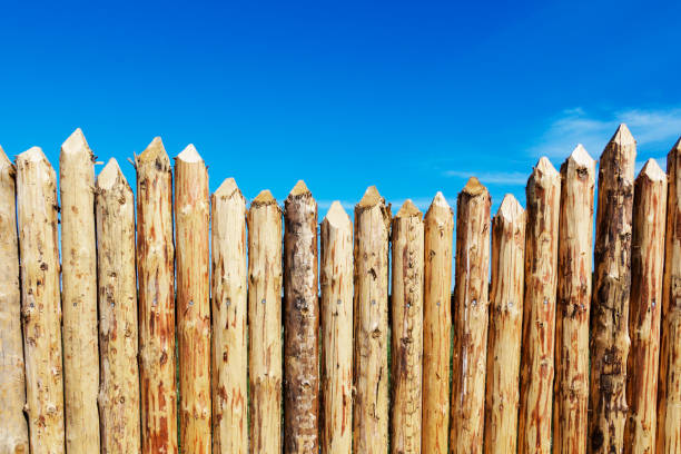 wooden fence made of sharpened planed logs. - palisade boundary stock photos and pictures