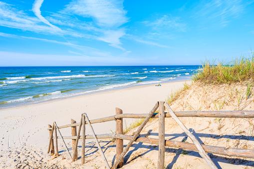 Wooden fence of entrance to sandy Bialogora beach, Baltic Sea, Poland