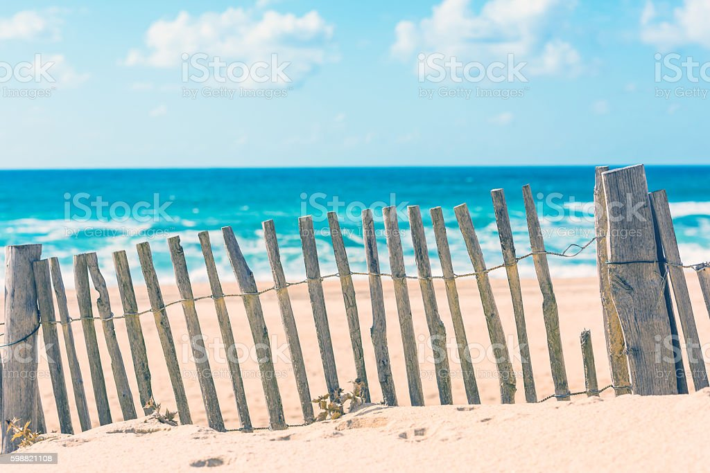 Wooden fence on an Atlantic beach in France stock photo