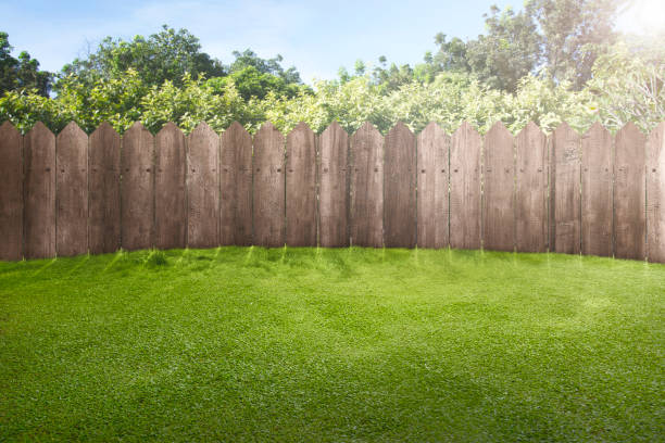 Wooden fence on green garden Wooden fence on green garden with sunlight background lawn stock pictures, royalty-free photos & images