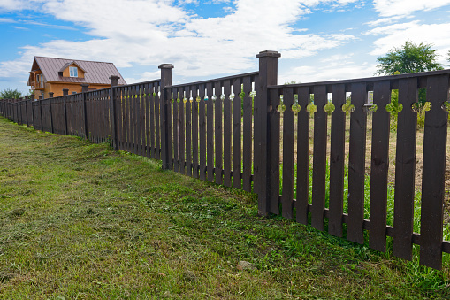 Wooden fence painted brown on a summer day