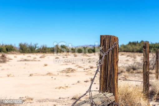 Wooden fence post with rusty barbed wire in a sandy field