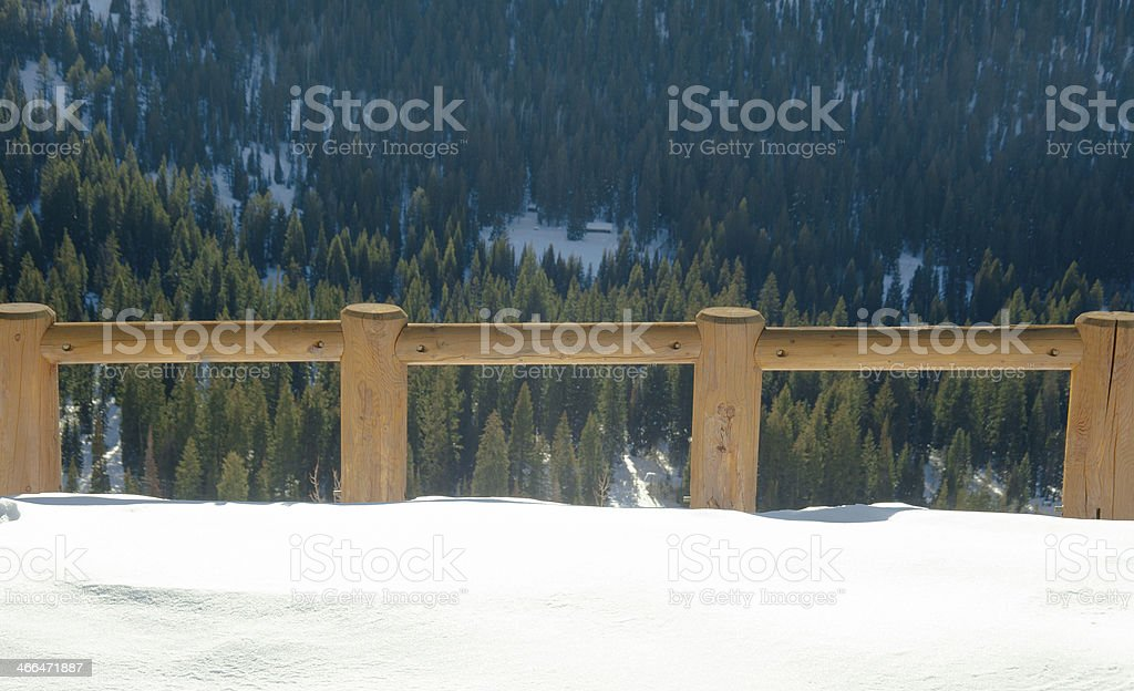Wooden Fence with snow and pine trees in the background royalty-free stock photo