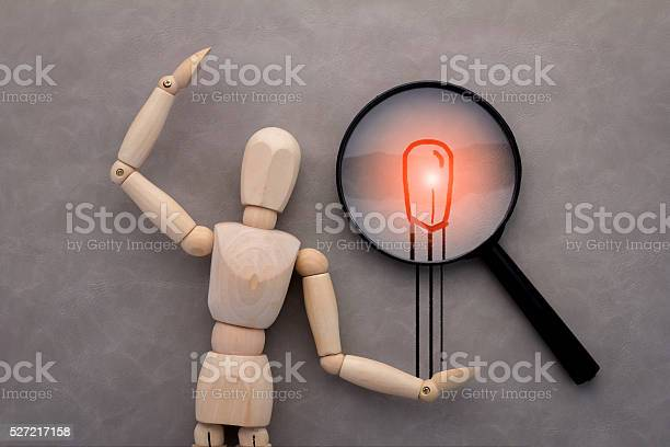 Wooden Figure And Drawing Of Match And Magnifyjpg Stock Photo - Download Image Now