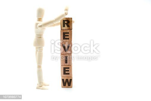 905689676 istock photo Wooden figure as businessman building Review as tower of wood cubes 1073593774