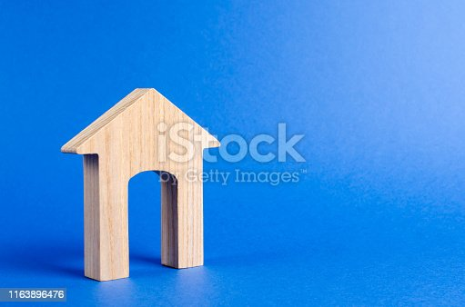 istock Wooden figure of a house with a large doorway on blue background. concept of buying and selling real estate, rent, investment. Home, Affordable housing, residential building. Construction buildings. 1163896476