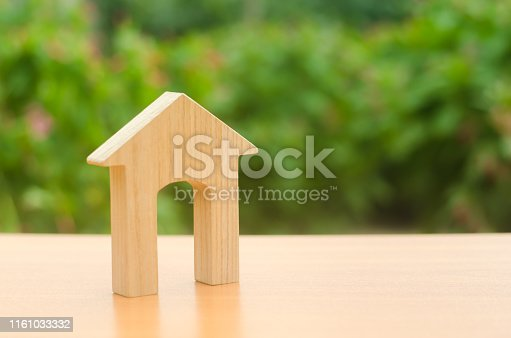 istock Wooden figure of a house with a large doorway on nature background. Home, Affordable housing, residential building. concept of buying and selling real estate, rent, investment and construction. 1161033332