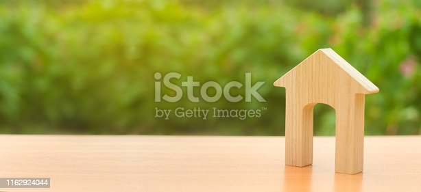 istock Wooden figure of a house with a large doorway on nature background. concept of buying and selling real estate, rent, investment. Home, Affordable housing, residential building. Copy space. Banner 1162924044