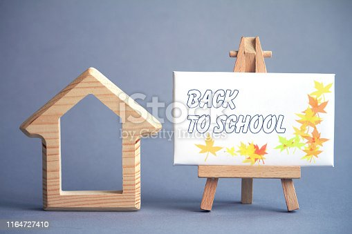istock Wooden figure of house on gray background and white board on miniature easel with the words Back to School, selective focus 1164727410