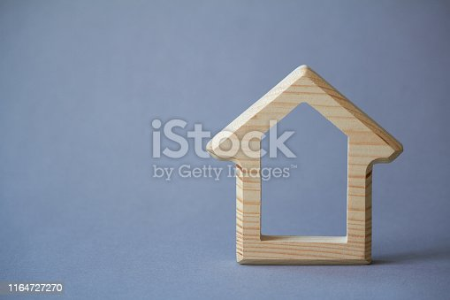 istock Wooden figure of house on gray background, the concept of buying or renting building, eco friendly to environment, selective focus 1164727270