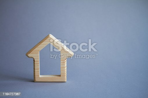 istock Wooden figure of house on gray background, the concept of buying or renting building, eco friendly to environment, selective focus 1164727387