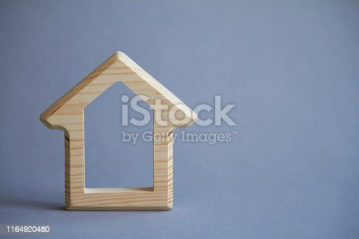 istock Wooden figure of house on gray background, the concept of buying or renting building, eco friendly to environment, selective focus 1164920480