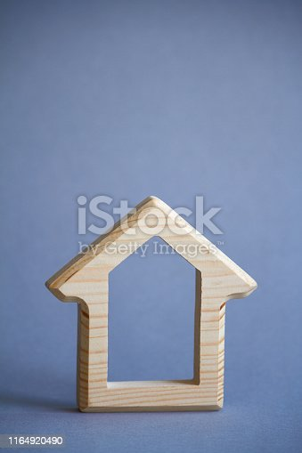 istock Wooden figure of house on gray background, the concept of buying or renting building, eco friendly to environment, selective focus 1164920490