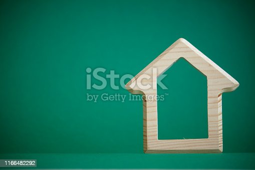 istock Wooden figure of house on green background, the concept of buying or renting building, eco friendly to environment, selective focus 1166482292