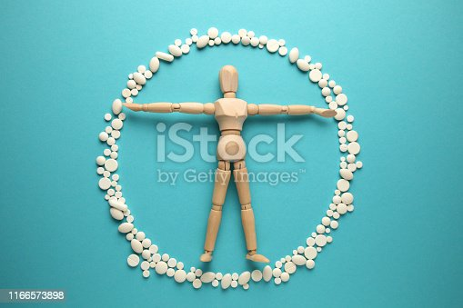 istock Wooden figure of man in protective ring of pills (antibiotics, probiotics and vitamins). Science is the guardian of health 1166573898