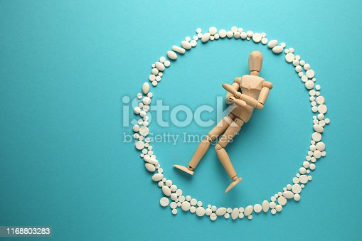 istock Wooden figure of man in protective ring of pills (antibiotics, probiotics and vitamins). Science is the guardian of health 1168803283