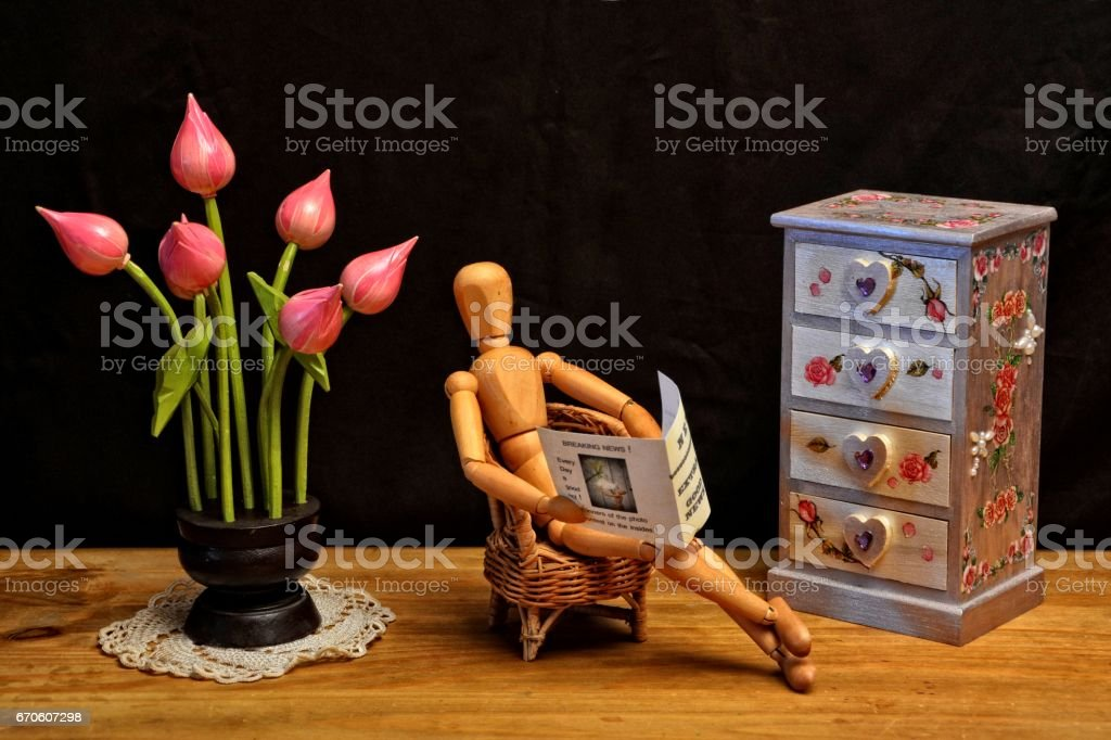 Wooden figure reading newspaper in living room stock photo