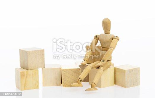 Wooden figure sitting on blocks.