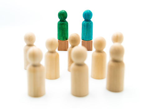 istock Wooden figures as a group listening to blue and green figures giving speech or debating, isolated on white background 1076575228
