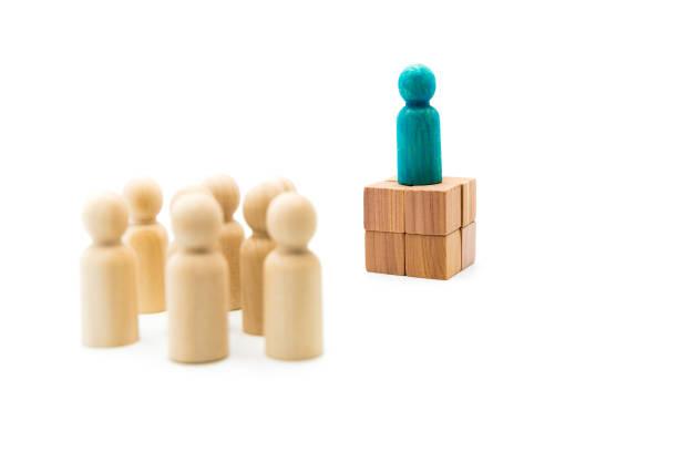 Figures en bois comme un groupe en écoutant un chiffre bleu helding, isolé sur fond blanc - Photo