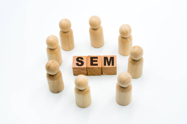 Wooden figures as business team in circle around acronym SEM Search Engine Marketing stock photo