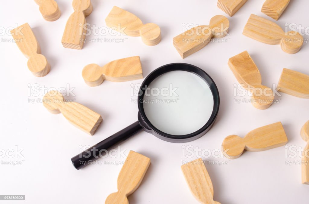 Wooden figures of people lie around a magnifying glass on a white background. Hiring for work, tracing people. The concept of the search for people and workers, human resources. stock photo