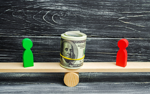 1018458132 istock photo wooden figures of people on scales and dollars between them. a dispute between two businessmen. trial. debt restructuring. wage arrears. protection of employee rights. court. Labor Law 1018457192