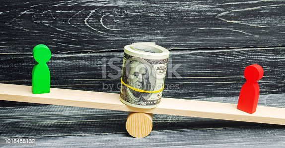 1018458132istockphoto wooden figures of people on scales and dollars between them. a dispute between two businessmen. trial. debt restructuring. wage arrears. protection of employee rights. court. Labor Law 1018458132