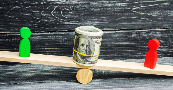 1018458132 istock photo wooden figures of people on scales and dollars between them. a dispute between two businessmen. trial. debt restructuring. wage arrears. protection of employee rights. court. Labor Law 1018458132