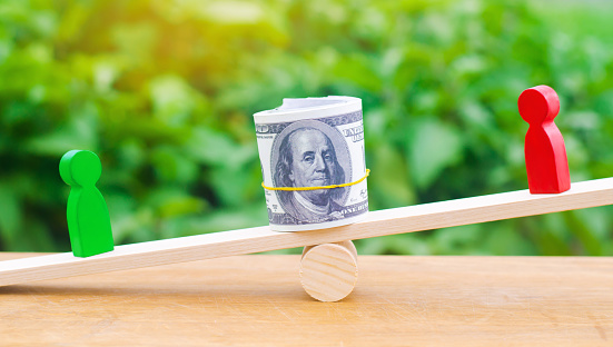 1018458132 istock photo wooden figures of people on scales and dollars between them. a dispute between two businessmen. trial. debt restructuring. wage arrears. protection of employee rights. court. Labor Law. court 1047795048