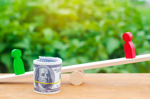1018458132 istock photo wooden figures of people on scales and dollars between them. a dispute between two businessmen. trial. debt restructuring. wage arrears. protection of employee rights. court. Labor Law. court 1047795050