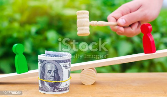 1018458132istockphoto wooden figures of people on scales and dollars between them. a dispute between two businessmen. trial. debt restructuring. wage arrears. protection of employee rights. court. Labor Law. court 1047795054