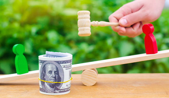 1018458132 istock photo wooden figures of people on scales and dollars between them. a dispute between two businessmen. trial. debt restructuring. wage arrears. protection of employee rights. court. Labor Law. court 1047795054