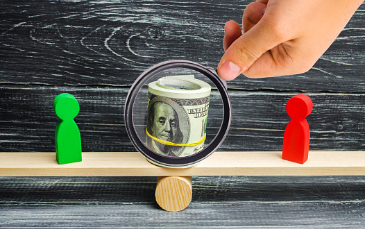 1018458132 istock photo wooden figures of people on scales and dollars between them. a dispute between two businessmen. trial. debt restructuring. wage arrears. protection of employee rights. court. Labor Law 1054976066