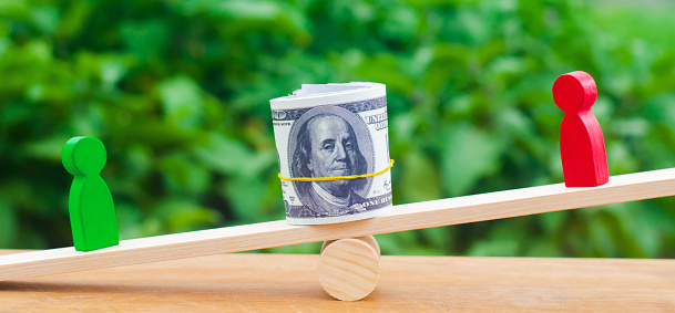 1018458132 istock photo wooden figures of people on scales and dollars between them. a dispute between two businessmen. trial. debt restructuring. wage arrears. protection of employee rights. court. Labor Law. court 1055880258