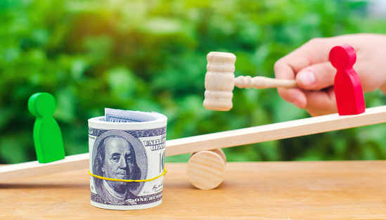 1018458132 istock photo wooden figures of people on scales and dollars between them. a dispute between two businessmen. trial. debt restructuring. wage arrears. protection of employee rights. court. Labor Law. court 1056657766