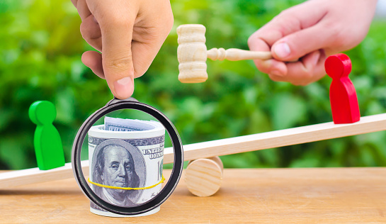1018458132 istock photo wooden figures of people on scales and dollars between them. a dispute between two businessmen. trial. debt restructuring. wage arrears. protection of employee rights. court. Labor Law. court 1063736000