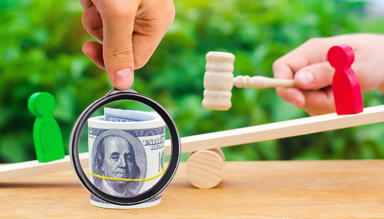 1018458132 istock photo wooden figures of people on scales and dollars between them. a dispute between two businessmen. trial. debt restructuring. wage arrears. protection of employee rights. court. Labor Law. court 1064929054