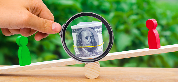 1018458132 istock photo wooden figures of people on scales and dollars between them. a dispute between two businessmen. trial. debt restructuring. wage arrears. protection of employee rights. court. Labor Law. court 1064932180