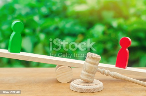 istock wooden figures of people. rivals in business stand on the scales. trial. conflict. victory and defeat. bad and good worker. the red figure outweighs the green one. competition. court 1047798340