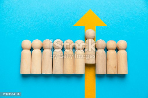 Wooden figures of people with a yellow arrow isolated on a blue background. Career and personal growth, business motivation.