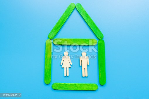 898212112 istock photo Wooden figures of the family stand in a wooden house. The concept of finding a new home, moving. A healthy strong family, continuation of the family and the birth of heirs. Quiet and peaceful life. 1224380212