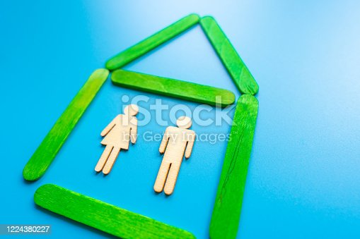 898212112 istock photo Wooden figures of the family stand in a wooden house. The concept of finding a new home, moving. A healthy strong family, continuation of the family and the birth of heirs. Quiet and peaceful life. 1224380227