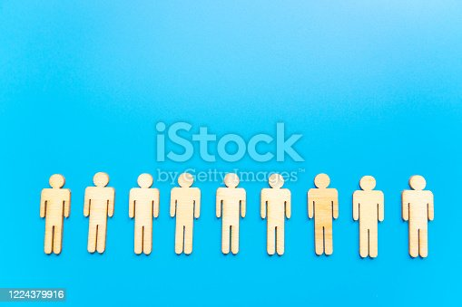 898212112 istock photo Wooden figures on blue background as a symbol of team building. Organization group people in business. Cooperation and partnership. 1224379916
