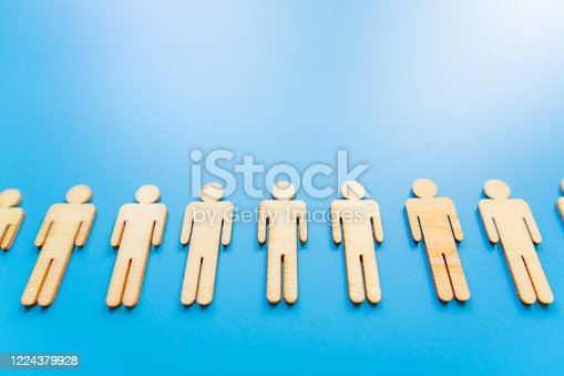 898212112 istock photo Wooden figures on blue background as a symbol of team building. Organization group people in business. Cooperation and partnership. 1224379928