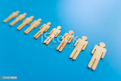 898212112 istock photo Wooden figures on blue background as a symbol of team building. Organization group people in business. Cooperation and partnership. 1224379946
