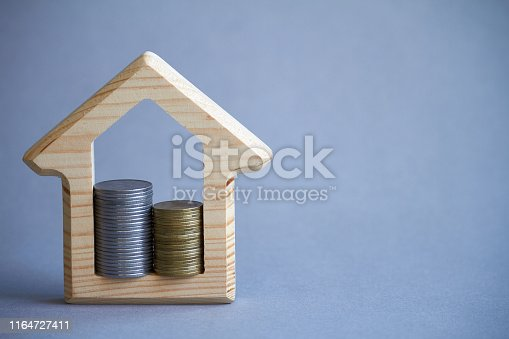 istock Wooden figurine of house and two columns of coins inside on gray background, the concept of buying or renting a building, eco-friendly to the environment, selective focus 1164727411