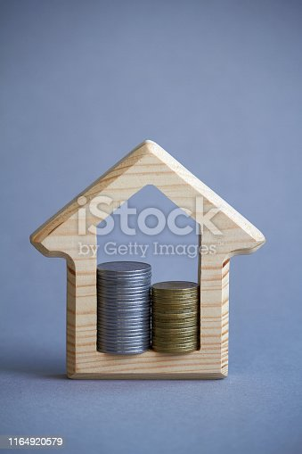 istock Wooden figurine of house and two columns of coins inside on gray background, the concept of buying or renting a building, eco-friendly to the environment, selective focus 1164920579
