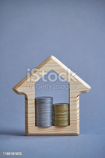 istock Wooden figurine of house and two columns of coins inside on gray background, the concept of buying or renting a building, eco-friendly to the environment, selective focus 1165181620