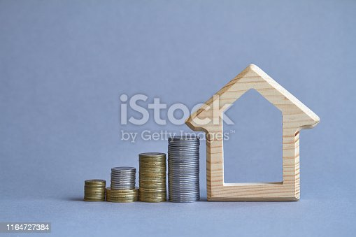 istock A wooden figurine of house with several columns of coins nearby on gray background, the concept of buying or renting a building, selective focus 1164727384